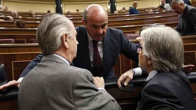 El ministro de Economía charla con otros diputados durante la sesión de control
