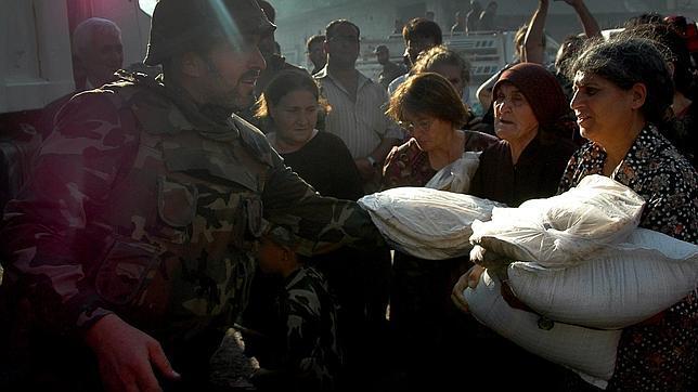 Un militar de Assad reparte ayuda entre los habitantes de Qusair este miércoles