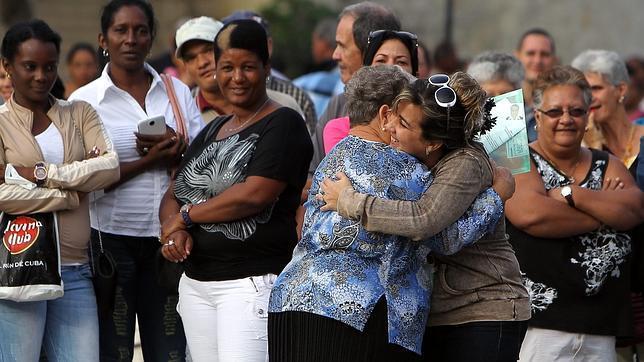 Dos mujeres se abrazan después de que una de ellas consiguiera visado para EE.UU., este martes en La Habana