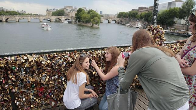 Turistas se toman una fotografía en el Pont des Arts