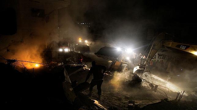Palestinos socorriendo a las víctimas de una casa arrasada por Israel