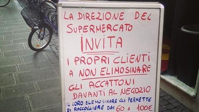 Cartel en el que se insta a no dar limosna a los mendigos en un supermercado de Ferrara