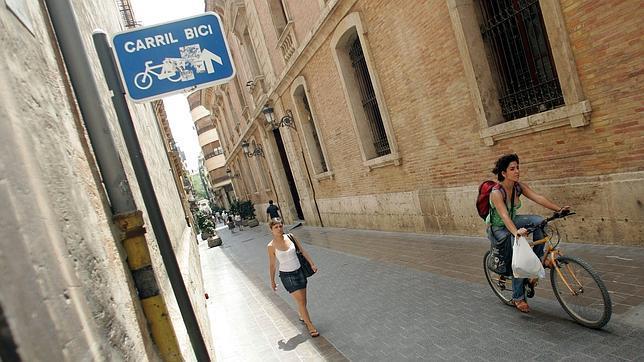 Una viandante y una ciclista transita por una zona de carril bici de Valencia