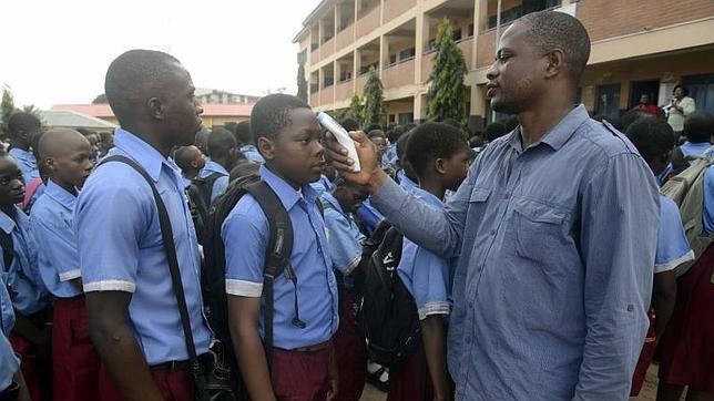Un profesor mide la temperatura de los alumnos en Lagos este miércoles
