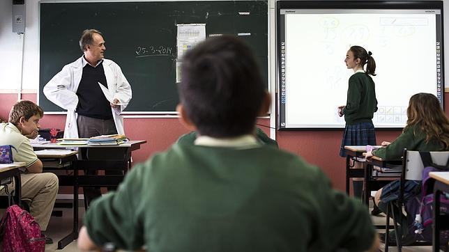 Un profesor examina oralmente a un alumna del colegio Los Sauces (Madrid)