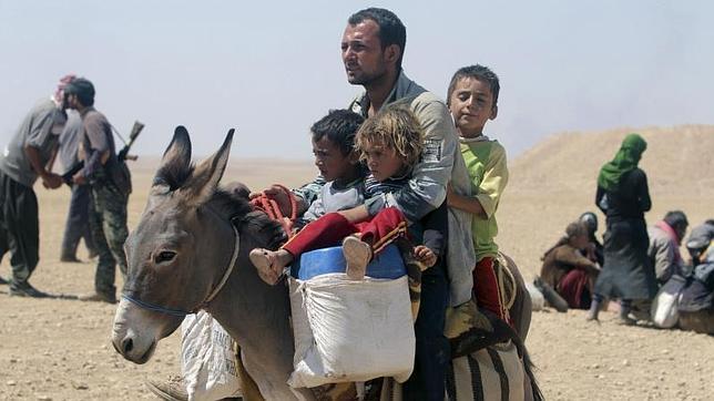 Refugiados cristianos y yasidies huyen hacia la frontera de Irak con Siria