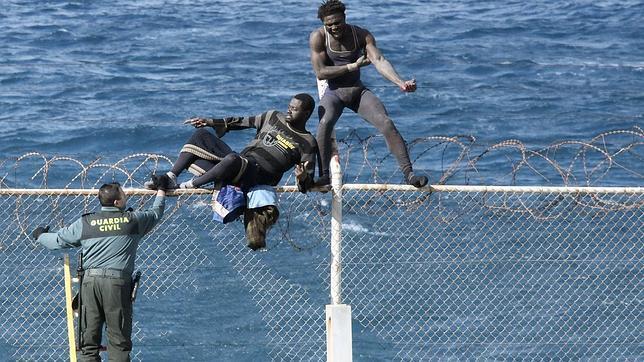 Dos inmigrantes intentan saltar la valla de Ceuta. Archivo