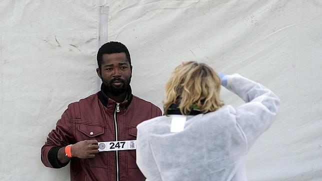 Un inmigrante llegado a Palermo tras el último nuafragio es fotografiado para el registro oficial