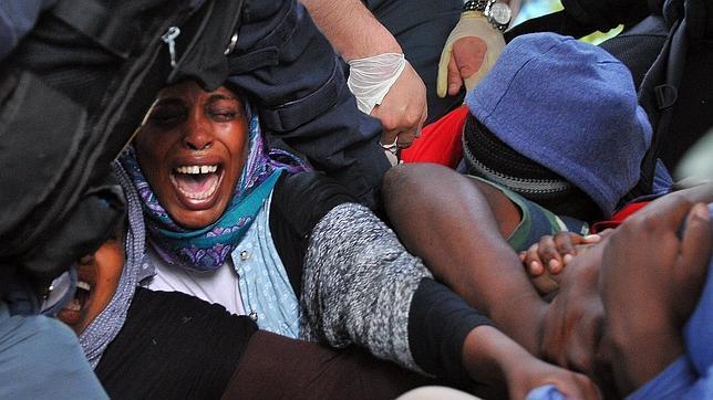 Inmigrantes indocumentados forcejean con los agentes de policía para evitar ser desalojados de los bajos de un puente ferroviario en la localidad fronteriza de Ventimiglia (Italia)