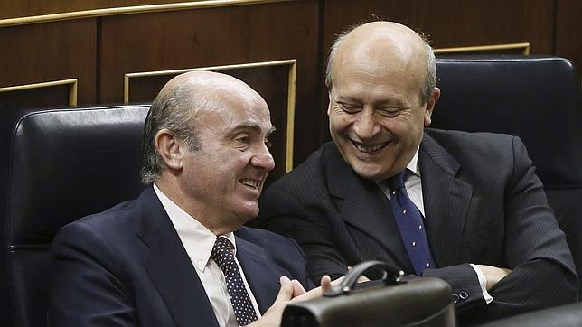 José Ignacio Wert hablando con el ministro de Economía, Luis de Guindos, durante la sesión de control al Gobierno