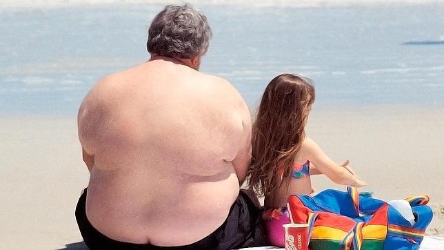 Un hombre junto a su hija en una playa