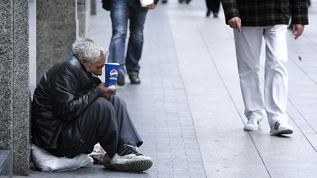 Un mendigo en el suelo de la gran vía madrileña