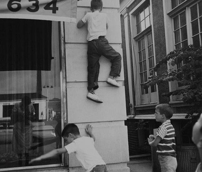 Vivian Maier fotografía su reflejo mientras unos niños juegan a su alrededor en Chicago