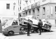 Dos policías supervisan una de las múltiples actuaciones de la grúa municipal en una céntrica calle. ABC