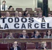 Mientras se llamaba a la votación, los parlamentarios de IU desplegaron una pancarta con el lema