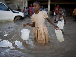 Dos niñas buscan un surtidor de agua potable en Gonaives, Haití. /AP