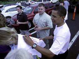 Obama le firma una camiseta a una 'fan', durante sus últimas vacaciones en Hawai. / Afp