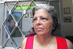REUTERS  Martha Beatriz Roque, de origen canario, observa una fotografía de Castro reflejada en la puerta de su casa de La Habana, en 2006