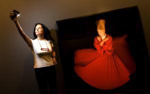 Isabel Muñoz, ayer en la Sala Canal, junto a una de sus fotografías de derviches danzando en éxtasis I FOTO IGNACIO GIL