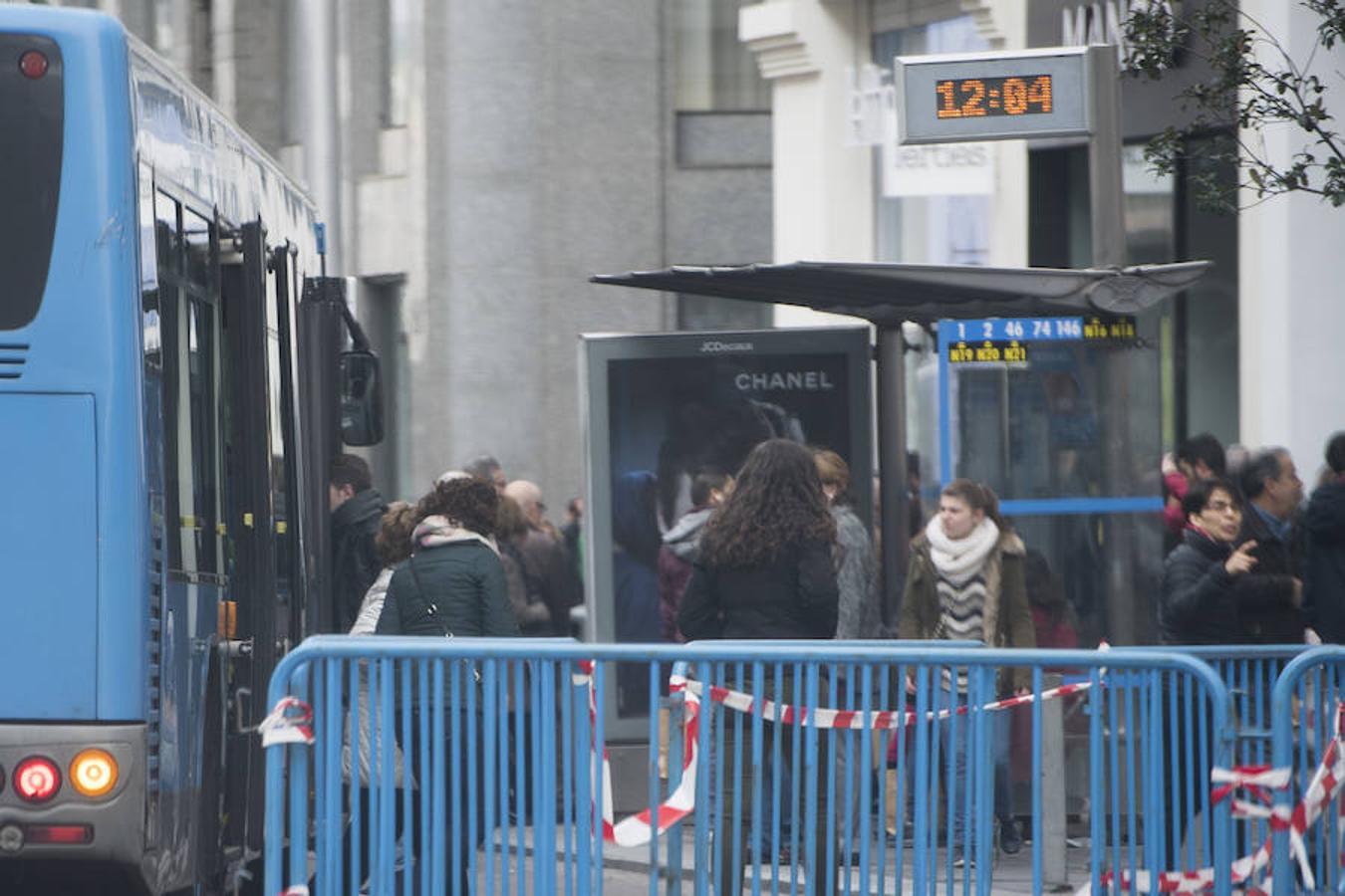 Varias personas esperan el autobús este sábado en la Gran Vía cortada