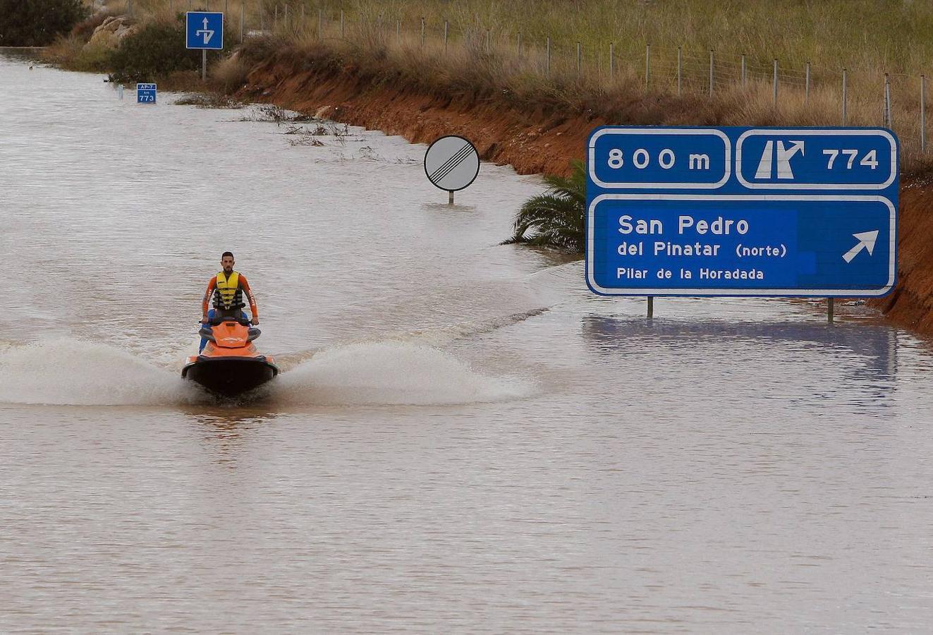 Un miembro de los servicios de rescate cruza en moto acuática la salida del túnel de la AP-7 a la altura del municipio alicantino Pilar de la Horadada