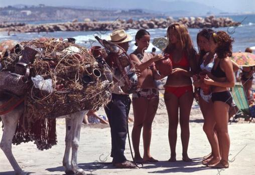 Un vendedor de cerámica con unas jóvenes turistas en bikini, mirando un botijo en 1966