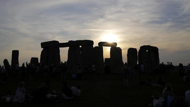 El sol sale tras el monumento de Stonehenge, conocido como «El Templo del Sol», durante el festival del Solsticio de Verano, en Reino Unido