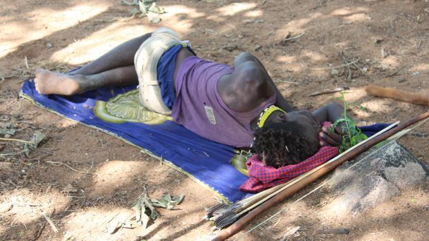 Un hombre Hadza duerme en el suelo en el norte de Tanzania