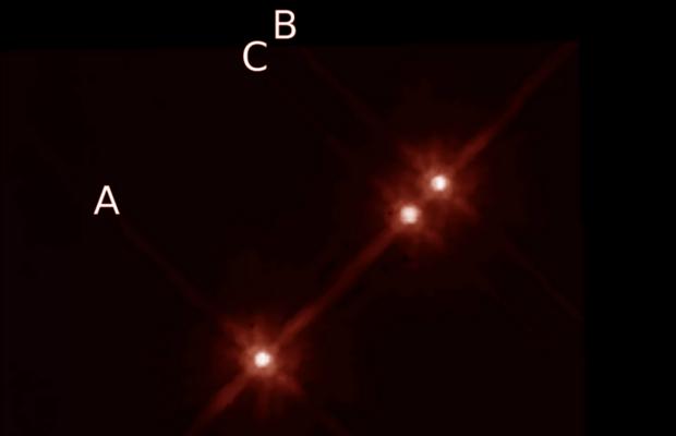 En la imegen de Telescopio Espacial Hubble se aprecian las tres estrellas de este sistema triple. El planeta fue descubierto en órbita de la estrella A.