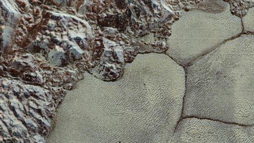 """Cerca de las montañas de hielo de agua en las franjas del noroeste del glaciar Sputnik de Plutón pueden proporcionar las partículas, y el """"corazón"""" de nitrógeno de Plutón proporciona vientos"""