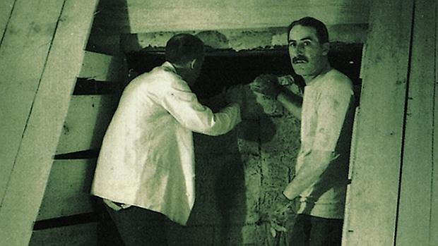 Lord Carnavon se asoma al interior de la cámara mortuoria de Tutankamón, junto a Howard Carter que mira a la cámara