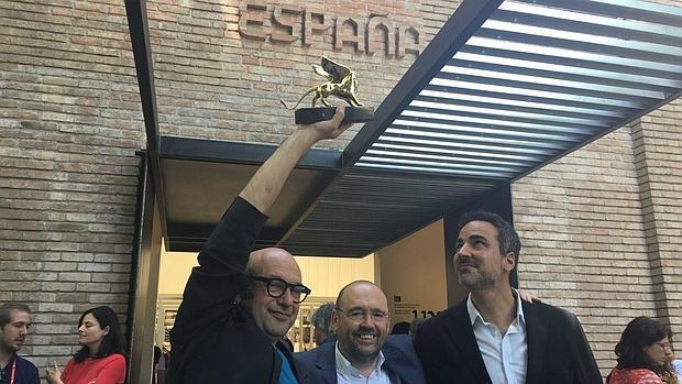 Carnicero y Quintáns posan sonrientes con el León de Oro en el exterior del Pabellón Español