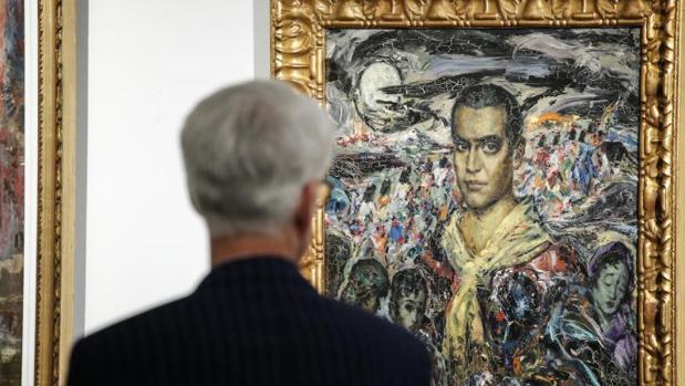 Un hombre observa el retrato de Federico García Lorca pintado por Enrique Ochoa