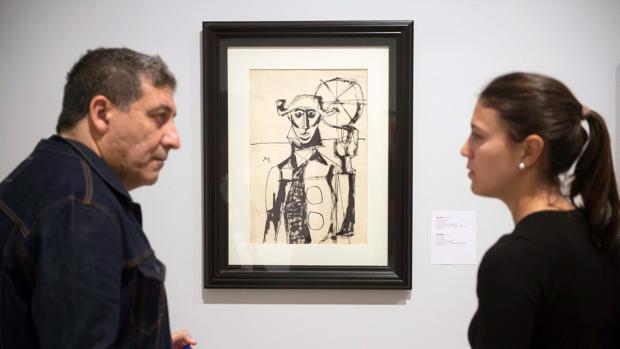 Dos personas, ante un dibujo de Millares, en el Centro Botín