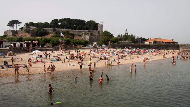 Turistas y vecinos se refrescan en la playa de Riveira en Baiona