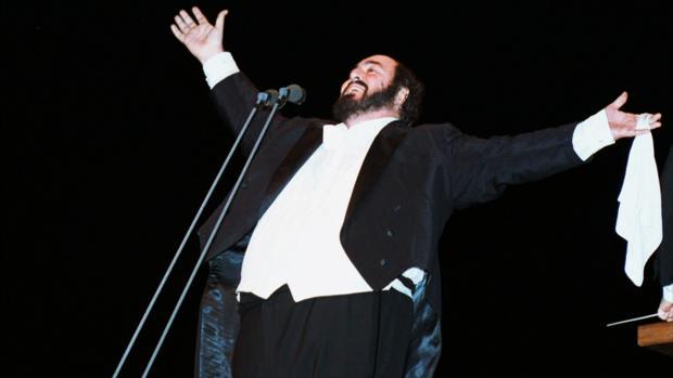 Luciano Pavarotti en una de sus poses características, «abrazando» al público y con el pañuelo en la mano