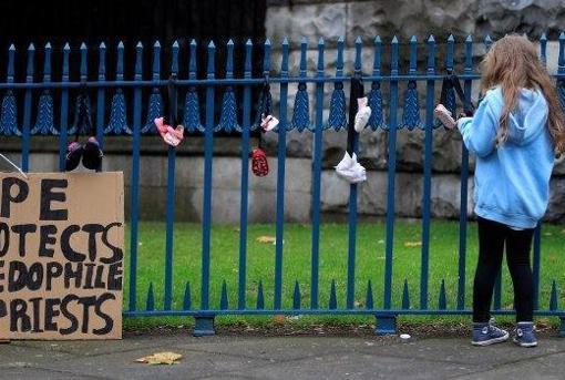 Zapatos de niños colgados a la entrada de la Catedral de Dublín como protesta simbólica contra la pederastia