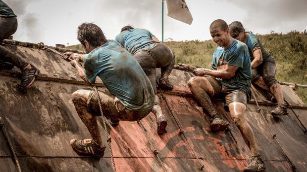 Unos participantes tratan de subir por un muro embarrado