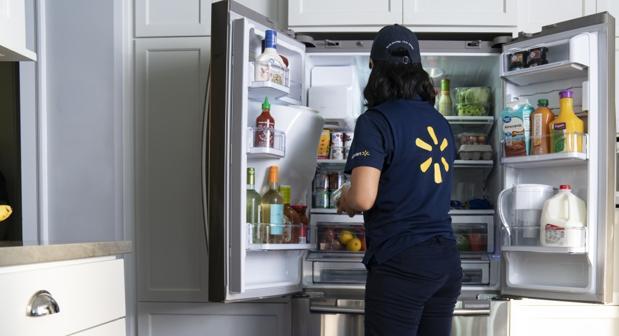Una empleada de Walmart coloca un pedido dentro del frigorífico