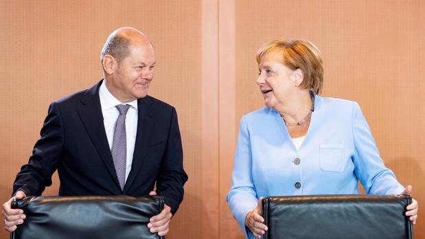 El ministro de Finanzas alemán, el socialdemócrata Olaf Scholz (izda) junto a la canciller alemana, Angela Merkel (dcha)