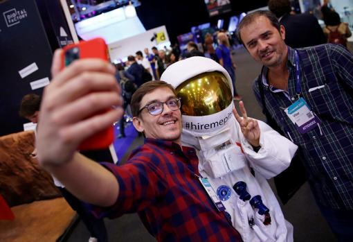 Dos visitantes se fotografían con una persona vestida de astronauta en la Web Summit