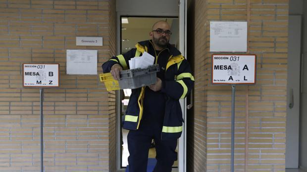 Un empleado lleva el voto por correo a un colegio electoral el 20-D
