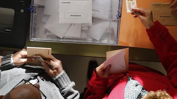 Dos españoles, ejerciendo su derecho al voto en un colegio electoral