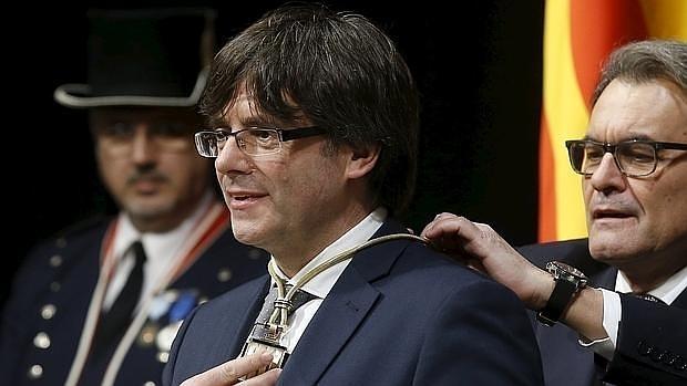 Artur Mas impone al nuevo presidente de la Generalitat, Carles Puigdemont, la medalla representativa del cargo