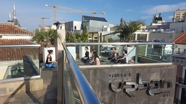 Sesión de yoga en la azotea del Hotel Urban, con las vistas del centro de Madrid al fondo