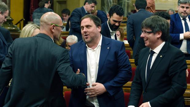 Romeva saluda a Oriol Junqueras en presencia de Carles Puigdemont, en el Parlamento de Cataluña