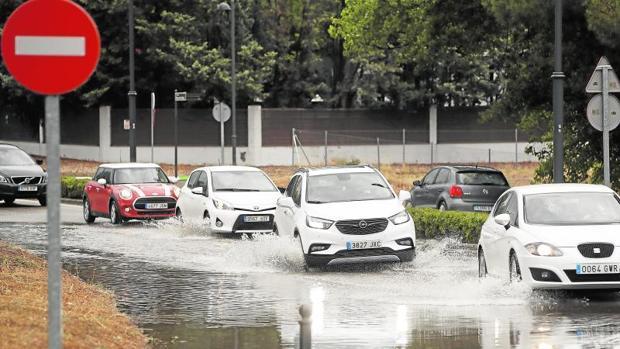 Varios coches circulan ayer por una calle inundada en Boadilla del Monte tras la tormenta