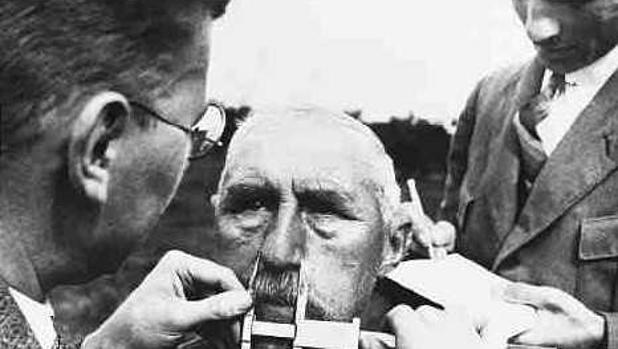 Científicos nazis midiendo el cráneo de un hombre en una exploración fuera de Alemania