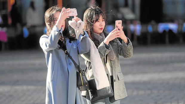 Dos turistas asiáticas toman fotografías en la Plaza Mayor