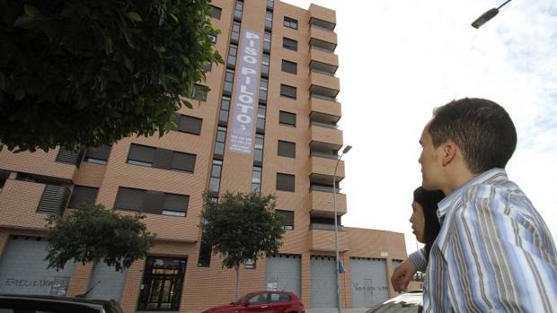 Una pareja observa un bloque de pisos en venta en Alicante